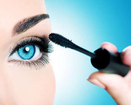 Macro shot of a women eye with long black eyelashes and makeup brush  -  studio photo