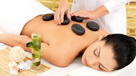 Foto de Woman having hot stone spa  massage of back in beauty salon - Imagen libre de derechos