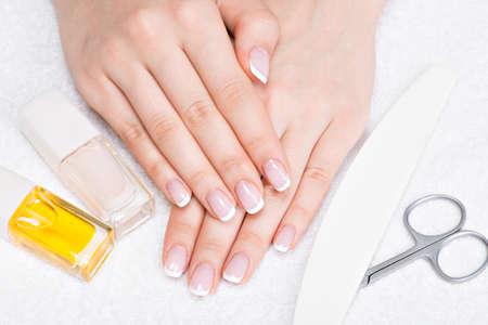 Foto de Woman in a nail salon receiving manicure by a beautician. Beauty treatment concept. - Imagen libre de derechos