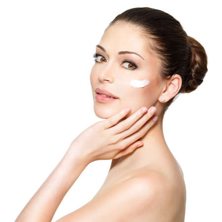 Photo pour Young woman with cosmetic  cream on a clean fresh face. Skin care concept - image libre de droit