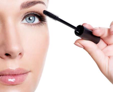 Young white woman applying mascara on eyelashes  - macro shot over white background