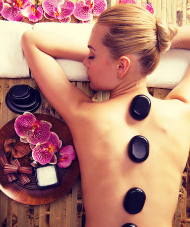 Foto de Beautiful woman relaxing in spa salon with hot stones on body. Beauty treatment therapy - Imagen libre de derechos