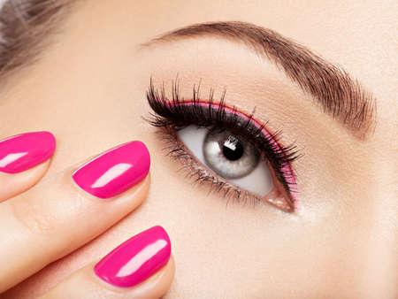 Foto de Closeup woman face with pink nails near eyes. Fingernails with pink manicure - Imagen libre de derechos