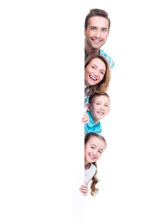 Foto de Young family with looking out of the banner - isolated on a white background - Imagen libre de derechos
