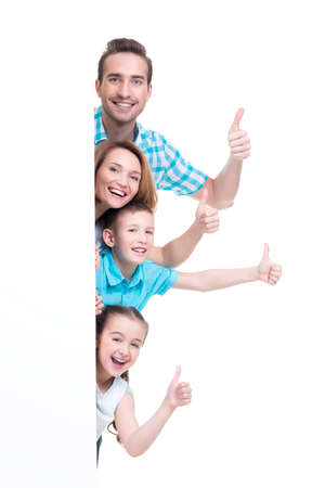 Photo pour Young family with a banner showing the thumbs-up sign - isolated on a white background - image libre de droit