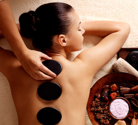 Photo for Young woman getting hot stone massage in spa salon. Beauty treatment concept. - Royalty Free Image
