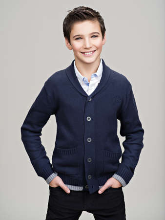 Foto de Happy pretty teenage boy posing at studio as a fashion model. - Imagen libre de derechos