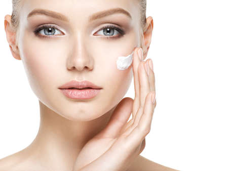Photo pour Young woman with cosmetic  cream on a clean fresh face - image libre de droit