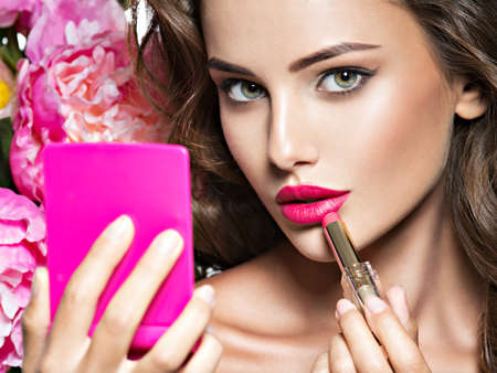 Photo pour Woman applying lipstick looking at mirror. Beautiful girl makes makeup - image libre de droit