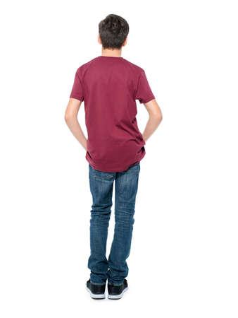 Photo pour Rear view, teen boy standing at studio over white background - image libre de droit