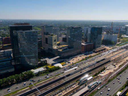 Photo pour Aerial of modern office buildings on the Amsterdam Zuidas business district connected by highway and train station - image libre de droit