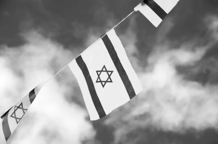 Israel flags in a chain in white and blue showing the Star of David hanging proudly for Israel\'s Independence Day (Yom Haatzmaut) - black and white