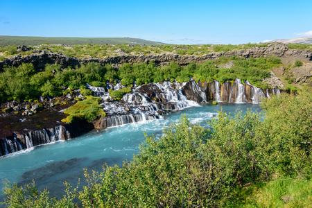Foto de Hraunfossar lava falls in Iceland, where water comes out of the porous lava rock as watterfalls - Imagen libre de derechos