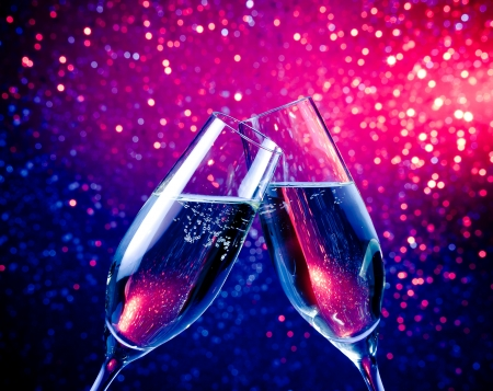 Photo for pair of a champagne flutes with bubbles make cheers on blue tint light bokeh background - Royalty Free Image
