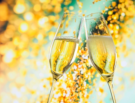Photo for a pair of champagne flutes with golden bubbles make cheers on golden light background with space for text - Royalty Free Image