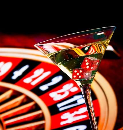 Foto de red dice in the cocktail glass in front of roulette wheel, casino series - Imagen libre de derechos