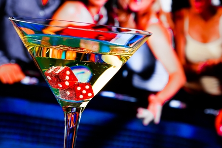 Foto de red dice in the cocktail glass in front of gambling table, casino series - Imagen libre de derechos
