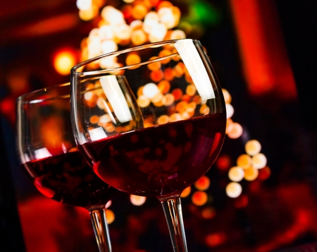 Foto de two red wine glass against christmas lights decoration background, christmas atmosphere - Imagen libre de derechos