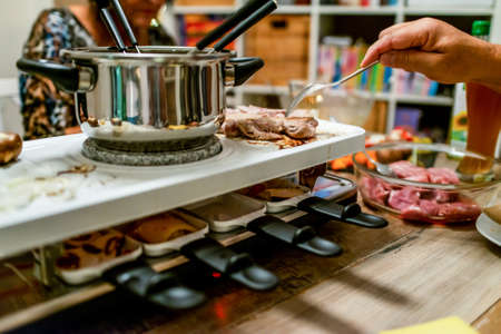 Foto de Swiss or Dutch raclette table filled with ingredients for a celebratory evening like Christmas or New Years Eve - Imagen libre de derechos