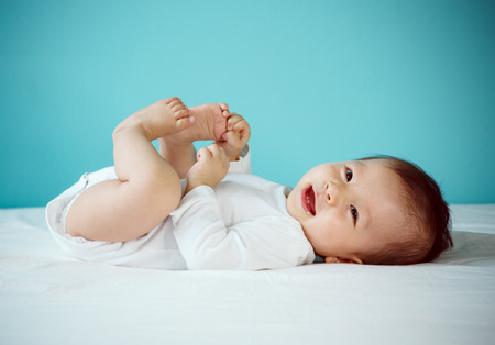 Foto de Portrait of a cute 7 months baby lying down on a bed new family and love concept. - Imagen libre de derechos