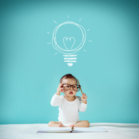 Foto de Concept idea of happy little baby with bulb at blackboard new family and love concept studio shot - Imagen libre de derechos