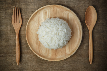 Foto de Top view of Thai jasmine rice in wooden dish with napery and wooden spoon - soft focus - Imagen libre de derechos