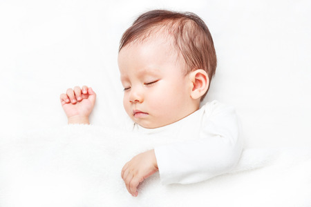 Photo pour Newborn sleeping on the white bed (isolated on white background) - image libre de droit