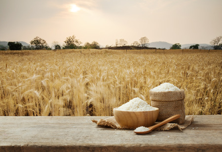 Foto de Jasmine Rice in bowl and burlap sack on wooden table with the golden rice field background - Imagen libre de derechos