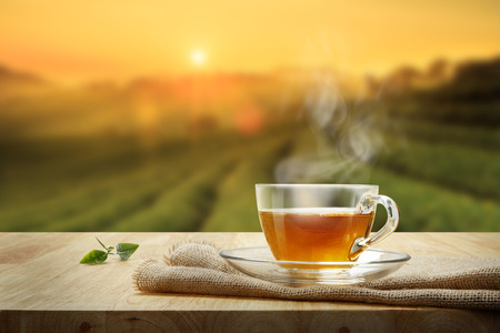 Photo for Cup of hot tea and tea leaf on the wooden table and the tea plantations background - Royalty Free Image