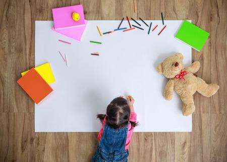 Foto de Little Asian girl drawing in paper on floor indoors, top view of child on floor with copy space - Imagen libre de derechos