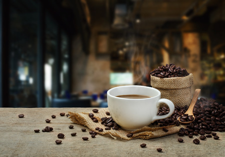 Foto de Hot Coffee cup with Coffee beans on the wooden table and the coffee shop background - Imagen libre de derechos