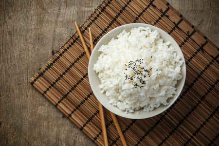 Photo for Steamed rice and black sesame seeds with chopsticks on a bamboo mat - Royalty Free Image