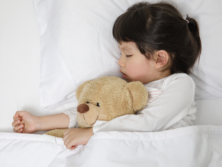 Foto de Child girl sleeping with teddy bear on the wooden bed in her bedroom, Happy asian child little girl with her teddy bear, family concept at home - Imagen libre de derechos