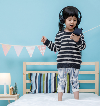Photo for Cute little girl sing a song with smartphone in her bedroom, Happy asian child little girl listening the music with headphone on the bed, technology concept - Royalty Free Image