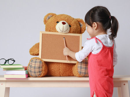 Photo pour Preschooler girl learns at school. Little girl having fun indoors at home, kindergarten or day care.  Educational concept for school kids. Cute child reading with teddy bear.  - image libre de droit