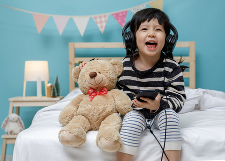 Foto de Cute little girl singing with smartphone with teddy bear in her bedroom, Happy asian child little girl listening the music with headphone with teddy bear on the bed, technology concept - Imagen libre de derechos