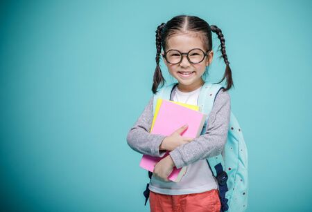 Photo pour Beautiful smiling Asian little girl with glasses and hold a books with school bag is back to school, empty space in studio shot isolated on colorful blue background, Educational concept for school - image libre de droit