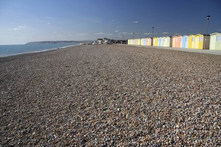 pebble beach at seaford head near newhaven in east sussex with row of colorful beach huts