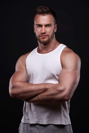 Photo for Studio portrait of athletic young man wearing white undershirt isolated on black background - Royalty Free Image