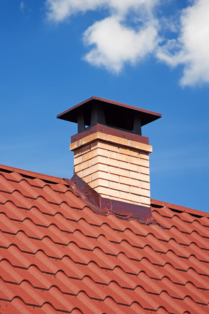 Photo pour Modern Ceramic Tile Roof with Chimney against the Sky extreme closeup. - image libre de droit