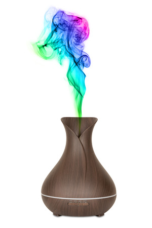 Photo pour Aromatherapy Concept. Wooden Electric Ultrasonic Essential Oil Aroma Diffuser and Humidifier with Colour Steam on a white background - image libre de droit