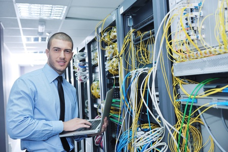 Foto de young engeneer business man with thin modern aluminium laptop in network server room - Imagen libre de derechos