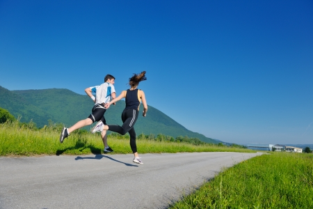 Foto de Young couple jogging in park at morning. Health and fitness. - Imagen libre de derechos