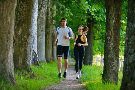 Foto de Young couple jogging in park at morning. Health and fitness. - Imagen libre de derechos