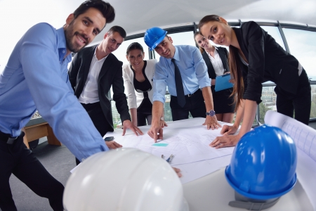 Foto de business people group on meeting and presentation  in bright modern office with construction engineer architect and worker looking building model and blueprint planbleprint plans - Imagen libre de derechos