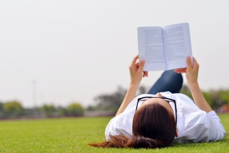 Photo pour Young student woman reading a book and study in the park - image libre de droit