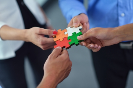 Foto per Group of business people assembling jigsaw puzzle and represent team support and help concept - Immagine Royalty Free