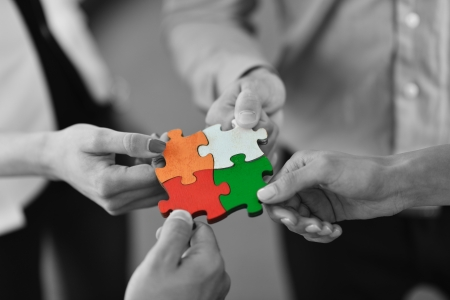 Foto de Group of business people assembling jigsaw puzzle and represent team support and help concept - Imagen libre de derechos
