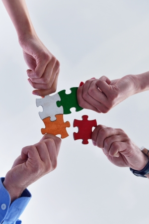 Photo pour Group of business people assembling jigsaw puzzle and represent team support and help concept - image libre de droit