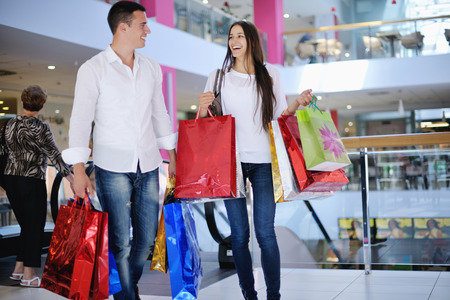 Photo pour happy young couple with bags in shopping centre mall - image libre de droit